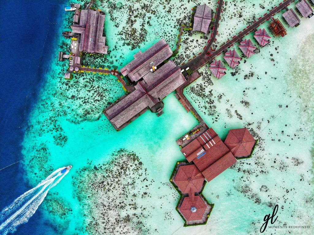 aerial view of sipadan kapalai beach resort wooden chalets and surrounding deep blue sea and turquoise lagoon with speedboat
