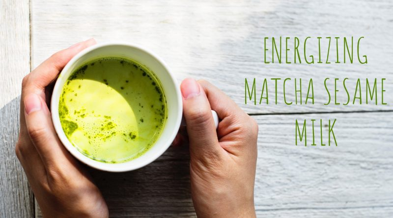 hands holding cup of matcha sesame milk