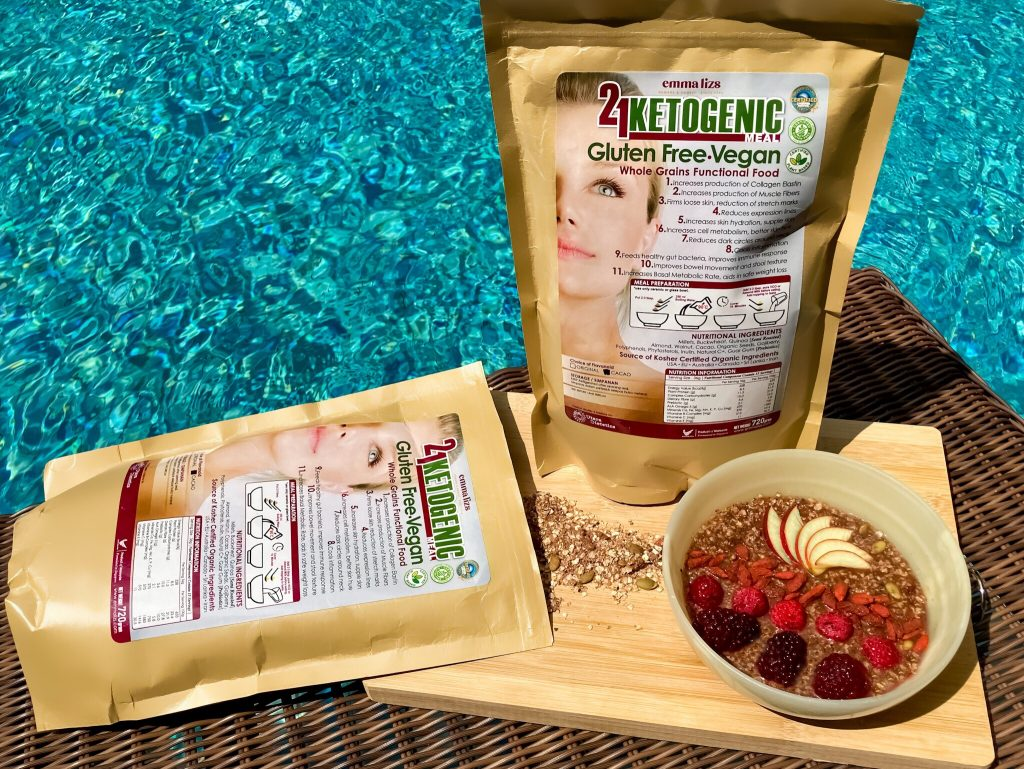 emma lizs 21 days ketogenic meal supplement packs on a wooden board with breakfast bowl of raw ingredients and fruits by the swimming pool