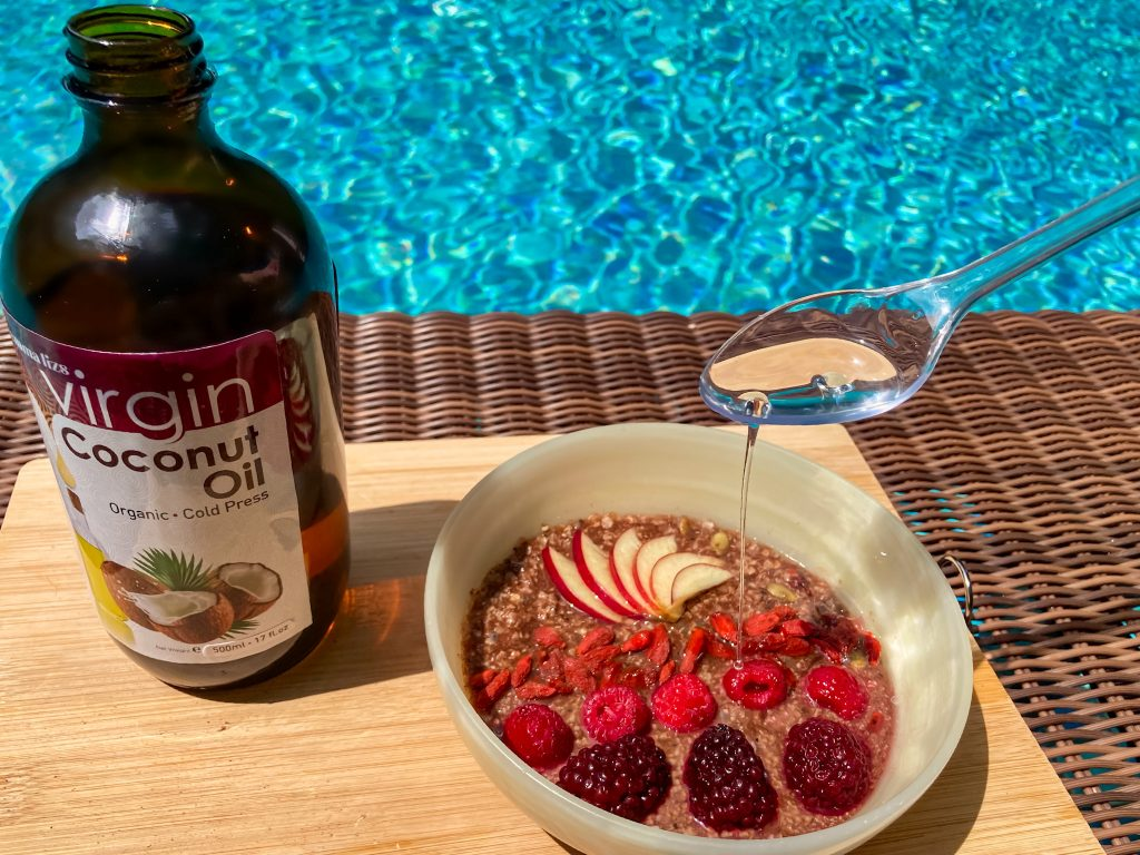 21 ketogenic meal breakfast bowl with fruits and a spoonful and a bottle of extra virgin coconut oil by the swimming pool
