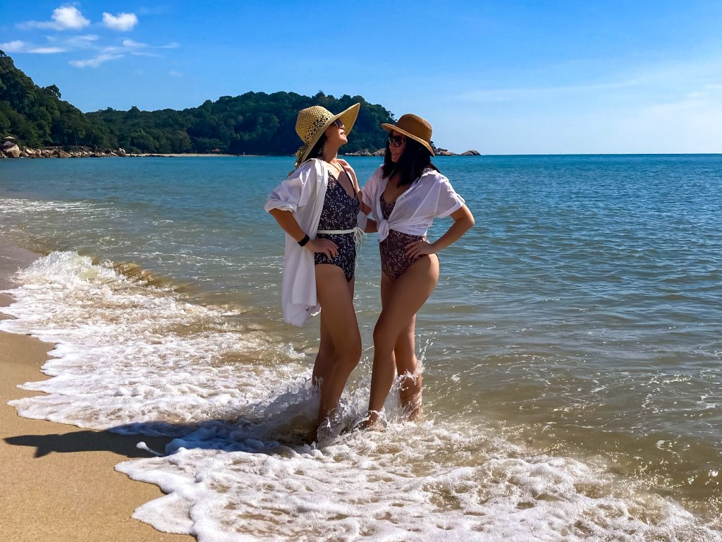 mother and adult daughter posing with swimwear and white shirts in the sea by the beach